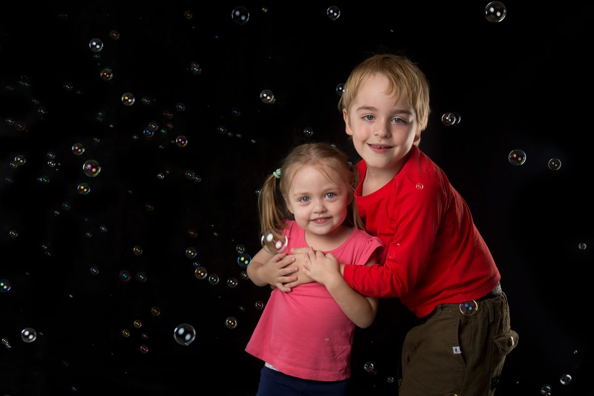 Brother and sister posing in between bubbles from professional bubble shoot in the photography studio