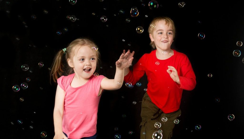 Kids having fun with professional bubble machine in the photography studio
