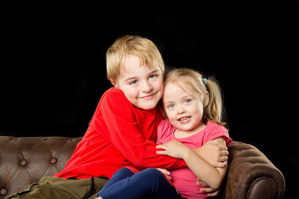 Brother and sister posing on our chesterfield sofa at bubble photo shoot in the photography studio