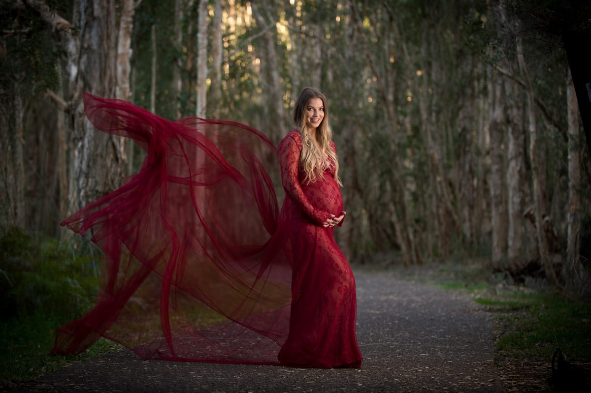 red maternity dress blowing up during maternity shoot